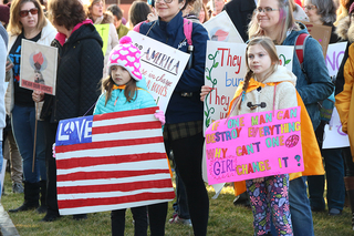 Two children hold signs. Many of the protesters at the Syracuse march included families.