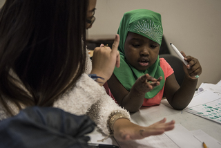 A volunteer helps a young girl with a math problem during RISE's after-school program, which takes place Monday to Thursday.